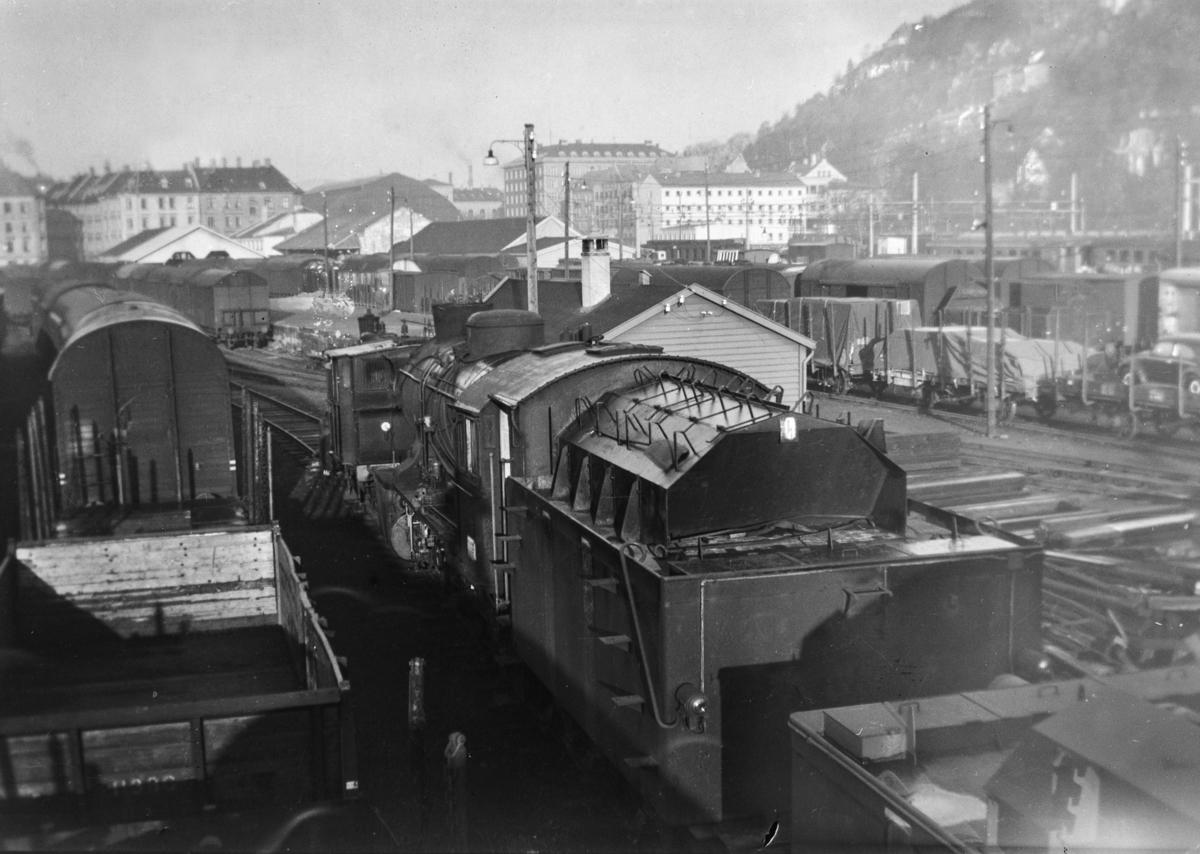 Bergen stasjon med diverse jernbanemateriell. Nærmes hensatt Damplokomotiv type 39a nr. 166, hugget hos Einar Cook, Nyhavn, Bergen, januar 1961.