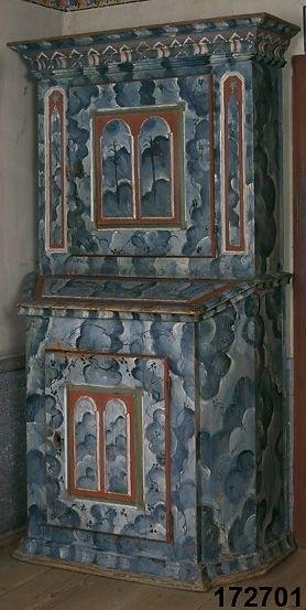 Skåp marmorerat i flera nyanser blått samt vitt, lister i rött, vitt och grönt. Överskåpet har 2 marmorerade speglar med sexuddiga stjärnor på var sida av skåpsluckan, skåpluckor på över- och underskåp har vardera 2 profilerade fyllningar. Klafflock till övre rum på underskåpet. Svängd skedhylla samt hylla i överskåpet.