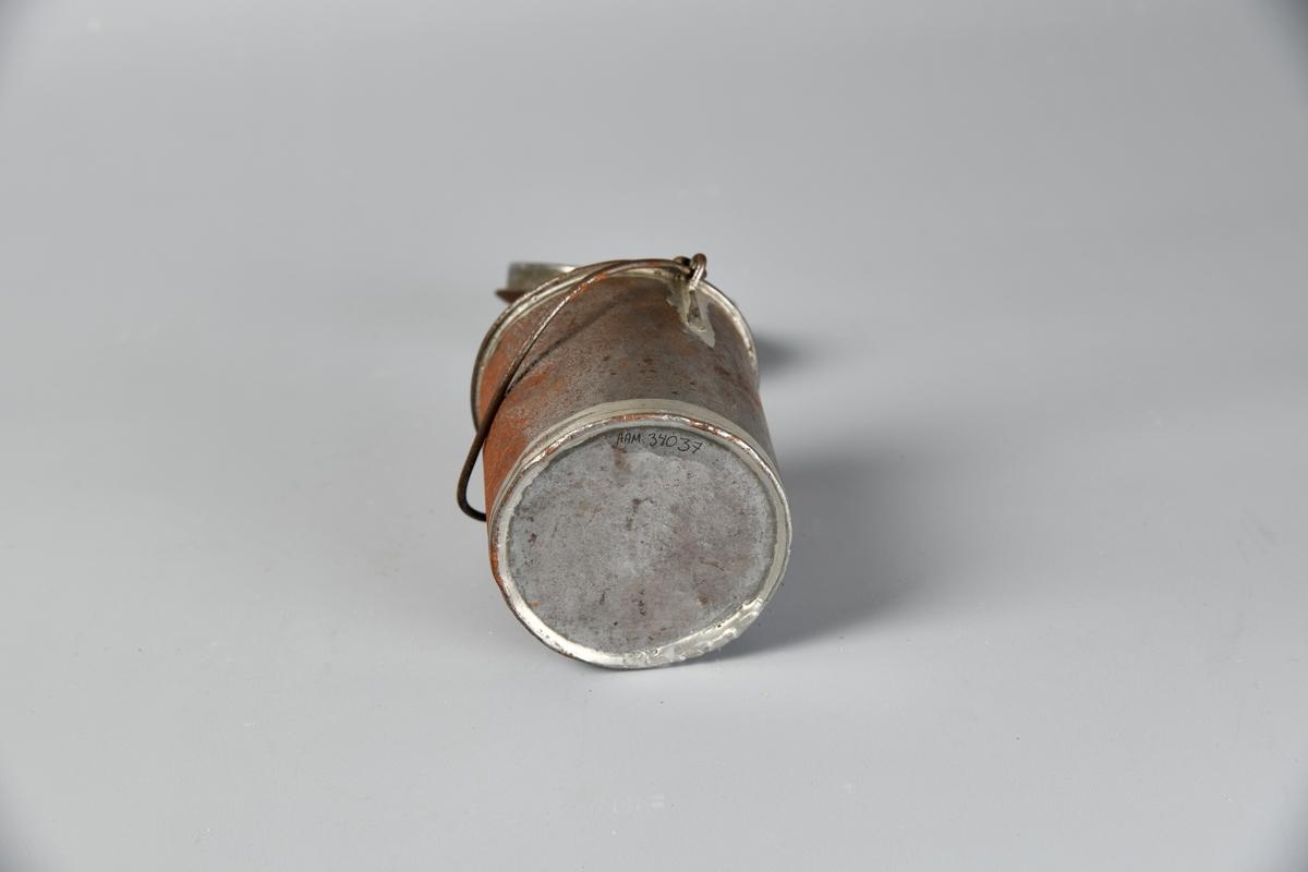 Spann med lokk. Håndtak på lokket og på hver side av korpus. Lokket er løst. Flere slike spann har blitt registrert som melkespann på Digitalt museum. Det er en del rust på oversiden av lokket og den ene siden av spannet.