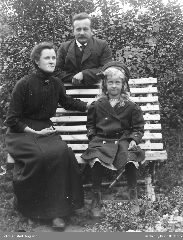 Portrett av ukjent familie på hagebenk.