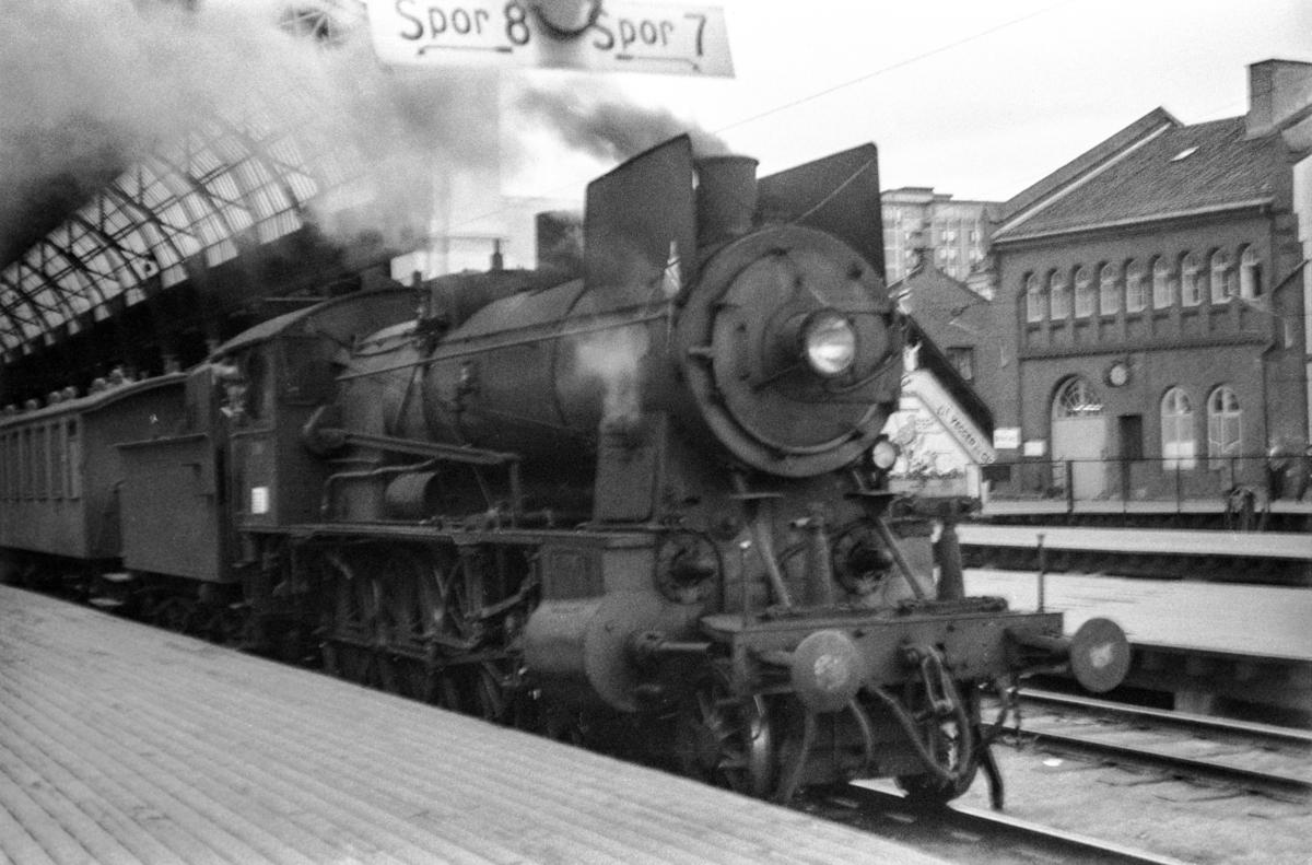 Persontog til Gjørvikbanen på Oslo Østbanestasjon. Toget trekkes av damplokomotiv type 30b nr. 348.