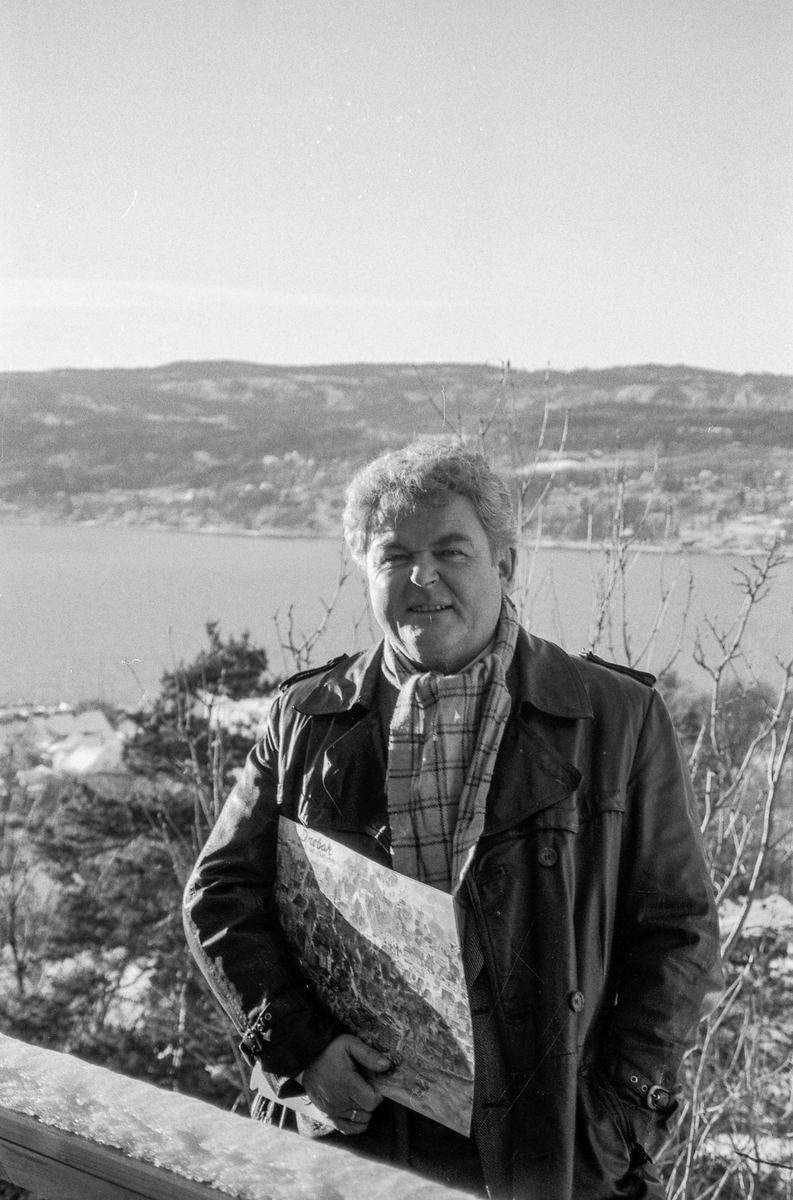 Kultursjef Olav Sandsmark i Frogn står på en kolle over Drøbak med plantegning/reguleringsplan under armen. Frogn; mann; Plantegning; vinter Drøbak frogn
