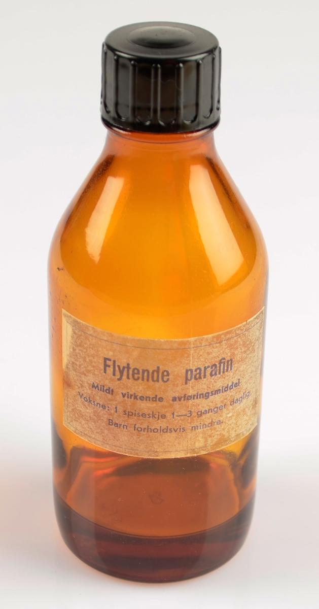 Brun glasflaske med skrukork med noko væske i. Flytende parafin, avføringsmiddel. Papiretikett med skrift i blått trykt på. Liten etikett på baksida.