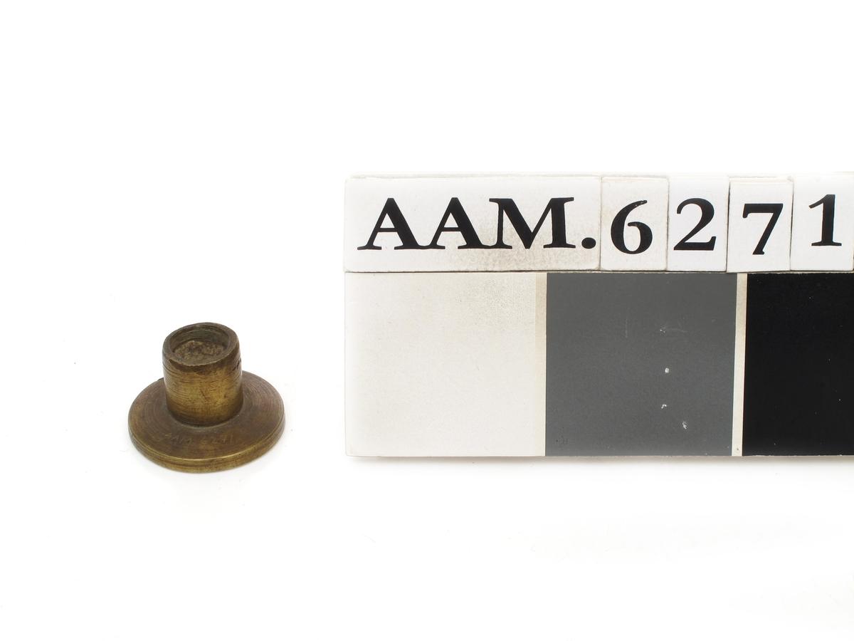 Rund messingplate med opphøyet kant og tekst i kraftige majuskler tvers over. Sylindrisk del på baksiden, avbrukket skaft.