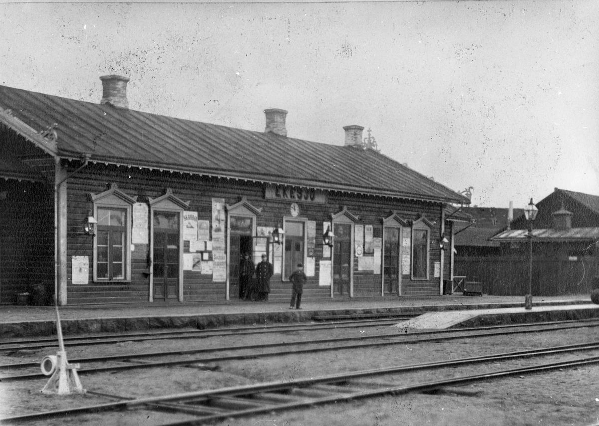 Eksjö gamla stationshus från 1873,  då hette stationen Ekesjö. Mannen i uniform vid dörren är troligen stationsföreståndare U E L Swensson.  Reklam: Skandia; Svenska Dagbladet.
