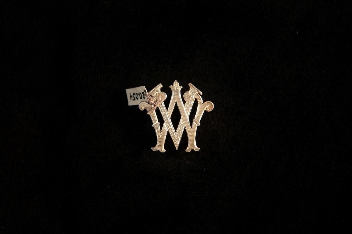 Ett väskmonogram av silver, bestående av ett sammanflätat  V och W (= Vivi Wallgren) med graverad dekor.