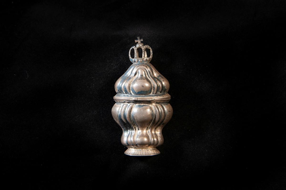 """En hög dosa av silver i rokoko. Dekorerad med s.k. """"knäckta åsar"""" i relief, ochhögst upp på locket en genombruten krona,med kors. Utländska stämplar i botten.Troligen dansk tillverkning. Jfr JM 18 742 och 19 952-953."""