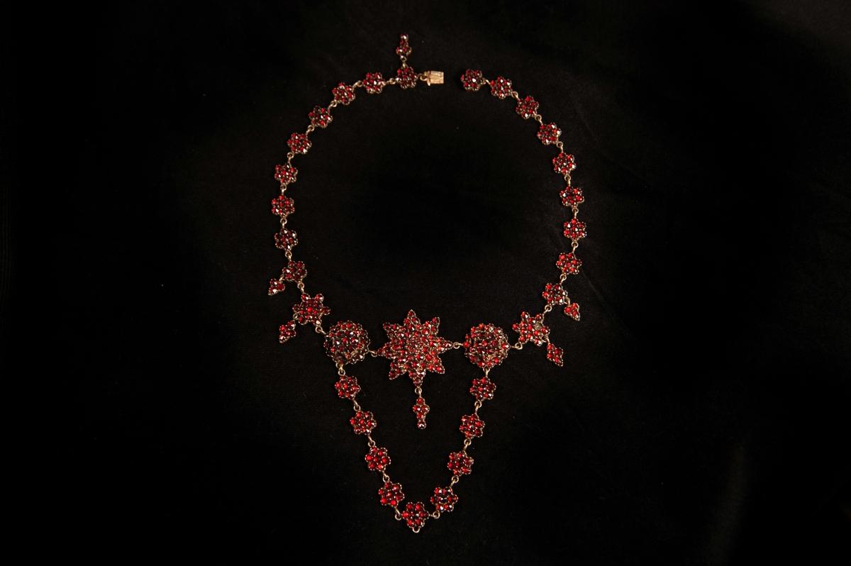 """Ett granathalsband med slipade röda granater, infattade i koppar. Halsbandet består av """"blommor"""" i länk, med två st. större """"blommor"""" i mitten, omgivande en stjärna med hänge. Från de två större blommorna hänger ner en blomlänk.Halsbandet ligger i rektangulär bleckplåtsask,fylld med vadd."""
