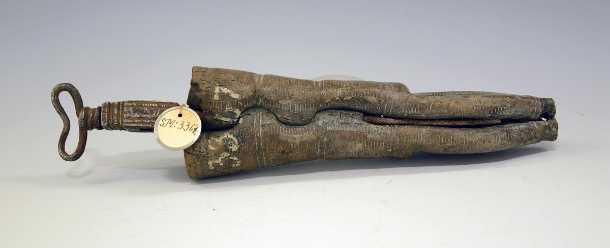 """Tvislire. Fra protokollen: Dobbeltknivslir. Jerngaffel i midten med hjerteformet top til aa hænge """"lekkje"""" i. Sliren skaaret streker som danner 4 kanter, samt kryds. Nederst: T.TS. 1730."""