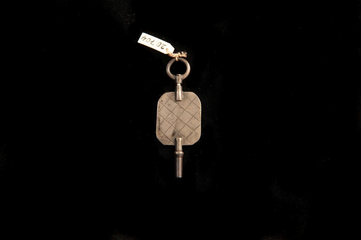 Enrnyckel av silver med fyrkantigt handtag. Rombformat rutmönster på ena sidan. I tillägg små graverade streck. På andra sidan bl a ett stiliserat hjärta med stämplar.