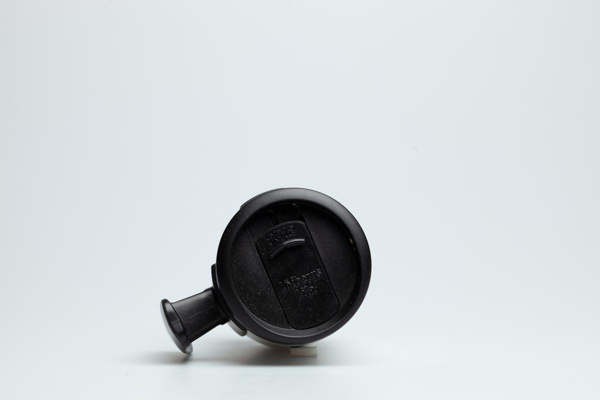 En hvit Statoilkopp med sort hank og med sort skrulokk. Skrulokket har en mekanisme som kan stenge og lukke for et lite hull, der man kan drikke kaffe igjennom. På skrulokket står det 2012 og Löfbergs Lila. Koppen er i grå metall på innsiden. Statoillogo i oransje på koppen.  Siden Statoilkoppen ble lansert i 2004 har den vært meget populær blant Norges bilister. Ved kjøp av koppen får bilisten gratis kaffe på alle Statoil stasjoner i landet, når bare vedkommende bruker Statoilkoppen. Det blir solgt ca. 400.000 Statoilkopper hvert år. Hvert år bytter koppen design.   Samlet inn I forbindelse med MiAs prosjekt Bensinstasjoner i Akershus 2016-2018.