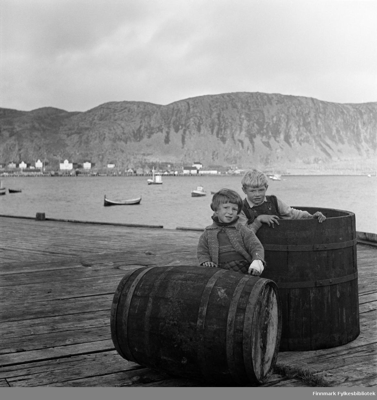 Åse Isaksen og Alf Nilsen (født 15.12.1933) på Nissen-kaia i Kjøllefjord, fotografert i 1940. Åse har bandasje på venstre arm med stor sikkerhetsnål. På andre siden av bukta sees flere fiskebruk og fiskemottak, hotell og boliger i Kjøllefjord. På fjorden ligger fiskebåter oppankret. En nordlandsbåt nærmest kamera. Åse har en strikket jakke og genser på seg og rutete skjørt eller bukser. Alf ser ut til å ha på seg snekkerbukser og skjorte. Sannsynligvis er dette på Nissenkaia.