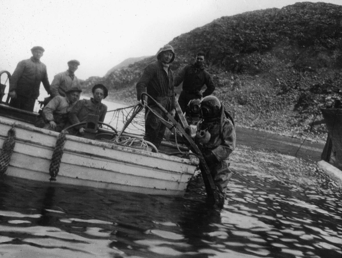 Hjelmdykker og mannskap i robåt. Hjelmdykkeren er på vei ut i vannet.