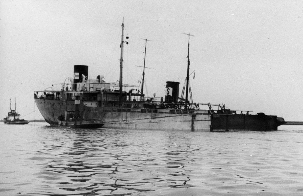 Motorskip på åpent hav, to dampslepebåter ved skipssiden.