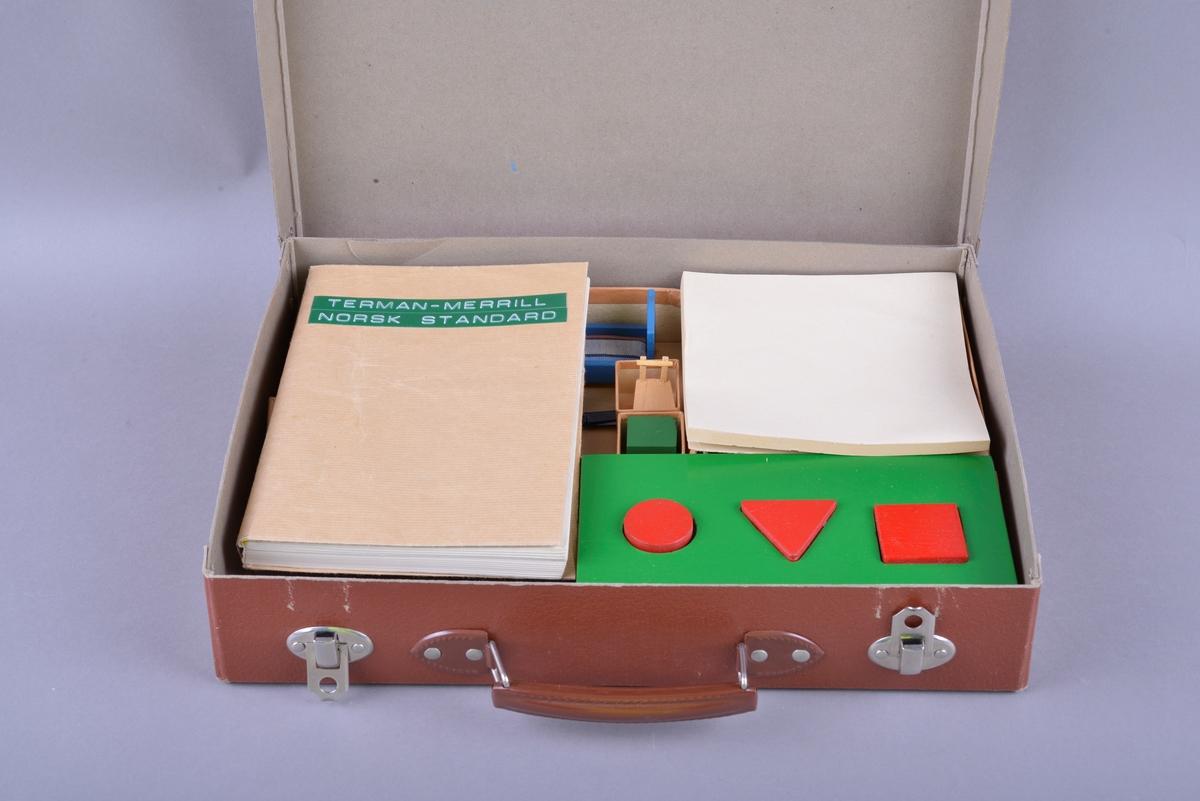 """Rektangulær brun koffert av papp, med håndtak og lås. Inne i kofferten er det små pappesker. Pappeskene inneholder små treklosser, plater med pålimte miniatyr-leker. Blant annet dukke, hund seng, saks, pipe. I tillegg er det flere små knapper, notatblokk og tekstilbånd. I kofferten ligger også en bok merket """"TERMAN-MERRILL // NORSK STANDARD""""."""