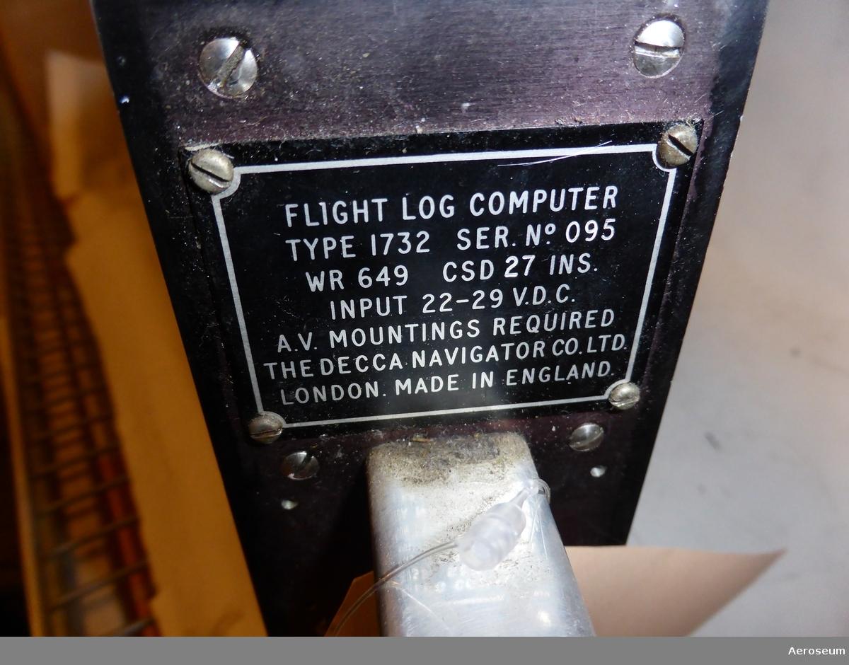 """En flight log computer, (Svarta lådan). Tillverkad av The Decca Navigator Company Ltd. Gjord i svart metall. Den är sliten, det finns skrapmärken i metallen.  På ena sidan står det: """"FLIGHT LOG COMPUTER TYPE 1732 SER. NO. 095 WR 649 CSD 27 INS. INPUT 22-29 V.D.C. A.V. MOUNTINGS REQUIRED THE DECCA NAVIGATOR CO. LTD. LONDON. MADE IN ENGLAND""""."""