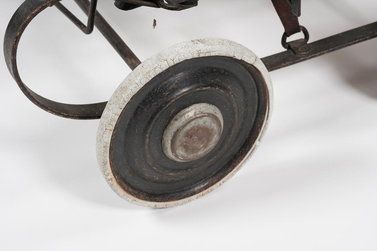 Setet henger i regulerbare reimer som er festet til trykkfjærene. Fjærene har form av en liggende C. Regulerbar rygg og fotbrett. Lærreim i forkant av setet. Håndtaket kan ved et enkelt håndgrep demonteres. På rammene som utgjør sidekanter og rygg er det festet forniklede beslag. Hjulene virker litt små til vogna; kan de være sekundære?