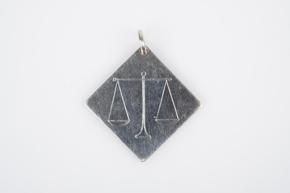 Et anheng i sølv. Anhengene er i kvadratisk form med inngravet navn og hilsen på den ene siden og inngravert symbol av stjernetegnet vektene på den andre siden.