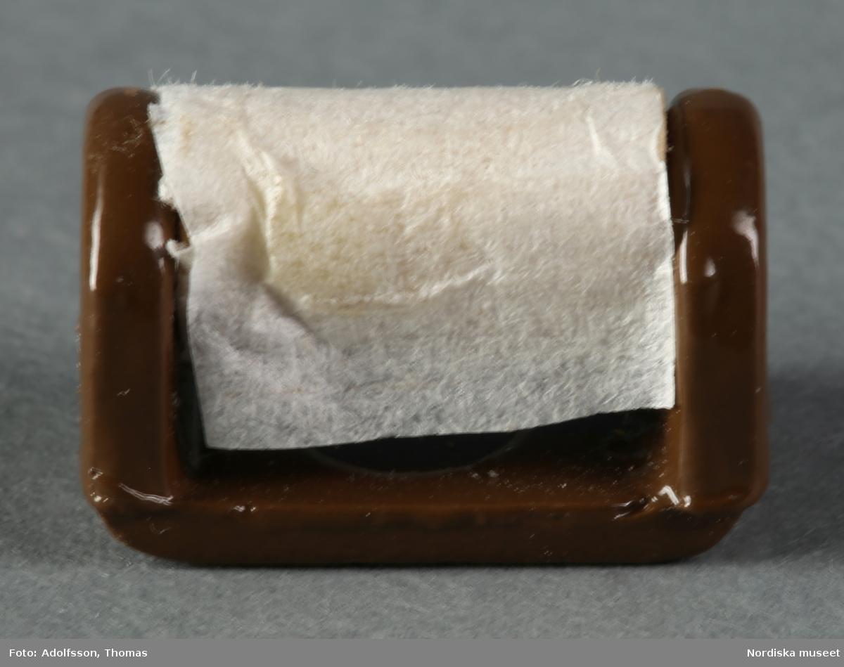 a) Toalettstol av porslin med blomdekor och plastlock, b) brun toalettpappershållare av metall och papper samt c) brun vaskrensare av metall. Hör till WC:t bredvid pojkrummet, andra våningen i dockskåp NM.0331721+.