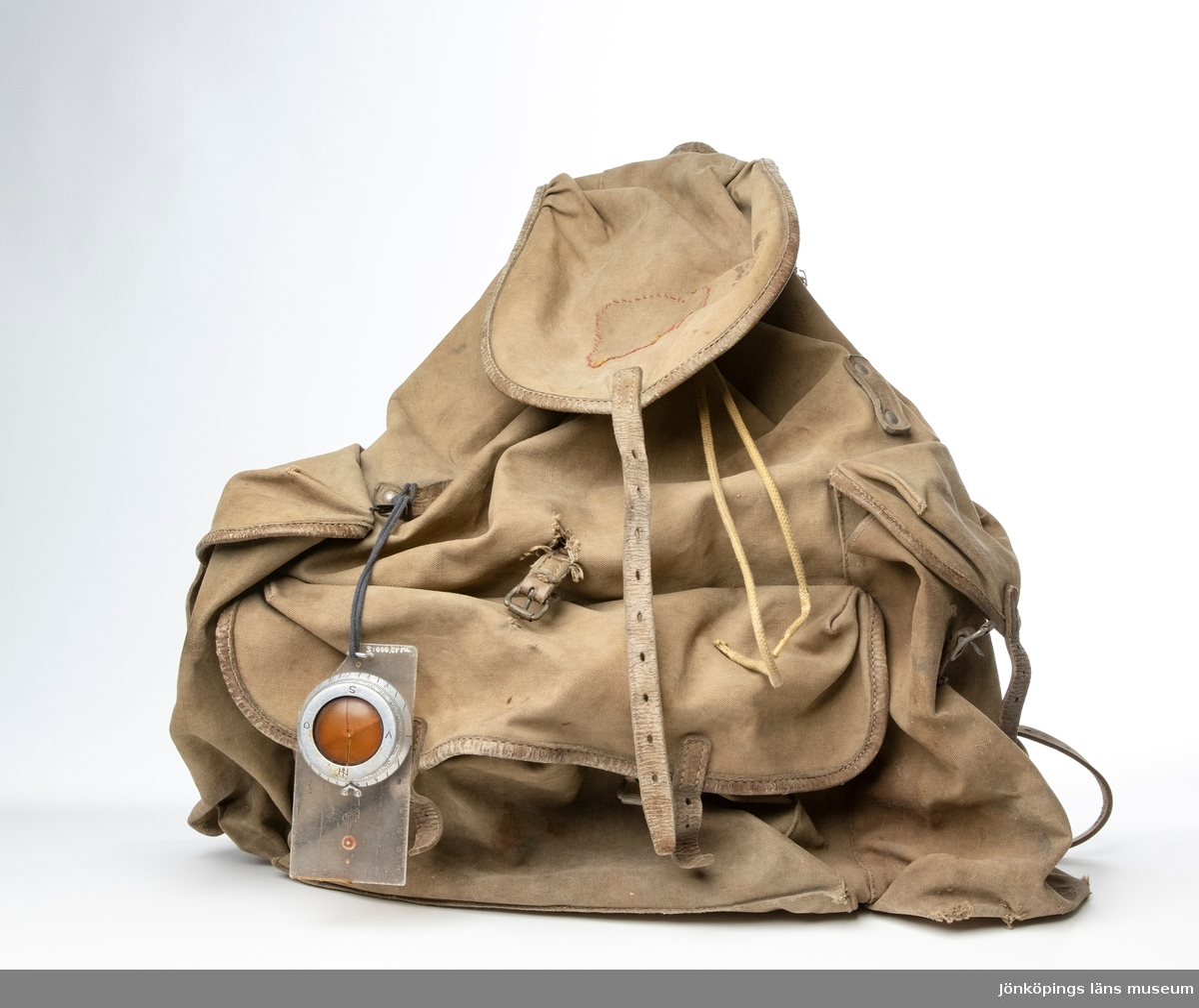 """Ryggsäck, modell Bergans Meis, bestående av triangelformad ram (mes), av metall, läderremmar och päronformad säck av kraftigt grå-brun bomullscanavas. Säcken har en stående ficka på var sida och en liggande nertill. Ryggsäcken är märkt: """"BERGANS MEIS OG RYGGSÆK SVERRE YOUNG PATENT WITHOUT WITH MADE IN OSLO. NORWAY"""". Säckens öppning är upptill under en lucka, och öppnas och tillsluts med hjälp av ett bomullssnöre samt ett lås av plast. Låset är märkt: """"Bergans OSLO NORWAY Patent Snorlås"""". Under firmamärkningen upptill är skrivet upp och ner: """"Gränsö"""". På undersidan av en av bärremmarna är skrivet namnet: """"Karl-Gustaf Fast. J.K.P.G.""""."""