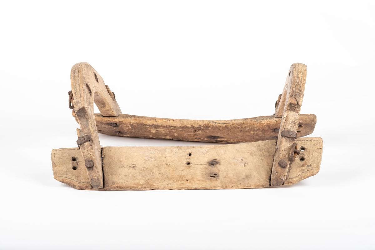 Sadelen består av to rette planker som skal ligge inntil hesteryggen. Det er borret tre par loddrette hull i begge plankene, to par hull i hver ende og to hull på midten. To bøyler er festet til plankene, disse har to utskårne kroker i hver side for oppheng av gjenstander hesten skal bære. Midt på den bakerste bøyla er det festet to jernkroker med ringer på baksiden. I den ene ringen er det knytt fast en tege- eller vidjestump. Den fremste bøyla har også jernringer, men de er festet ved de utskårne krokene i treverket. På bøylene er det dekorasjosborder langs hele undersiden, på forsiden, baksiden og oversiden av bøylene.