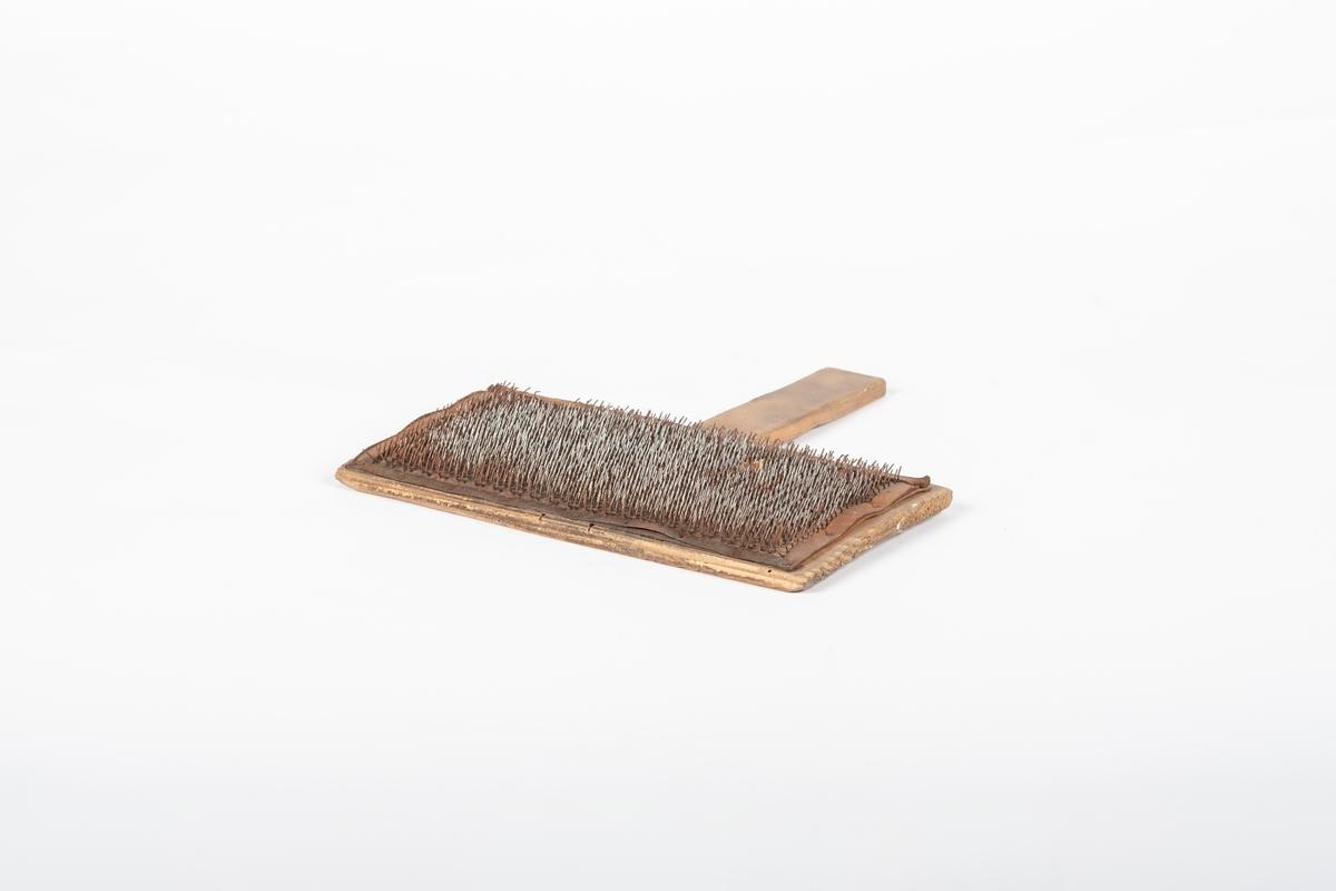 Karden består av et trestykke med innfelt håndtak og med lærstykke fullt av små metallstenger som er festet til trestykket.