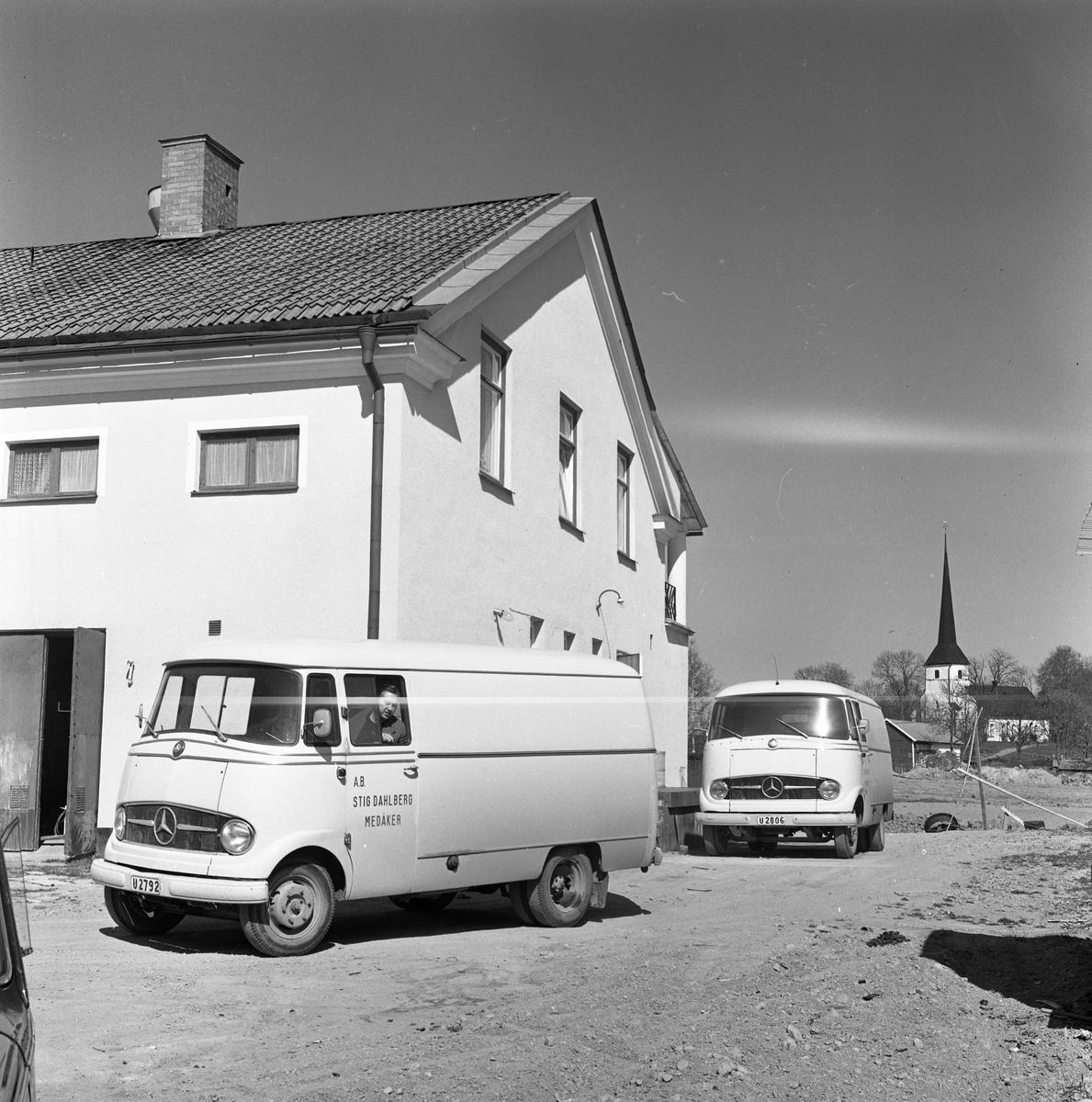 Två skåpbilar, för mattransporter, utanför AB Stig Dahlberg Storkök. Medåkers kyrka i bakgrunden.