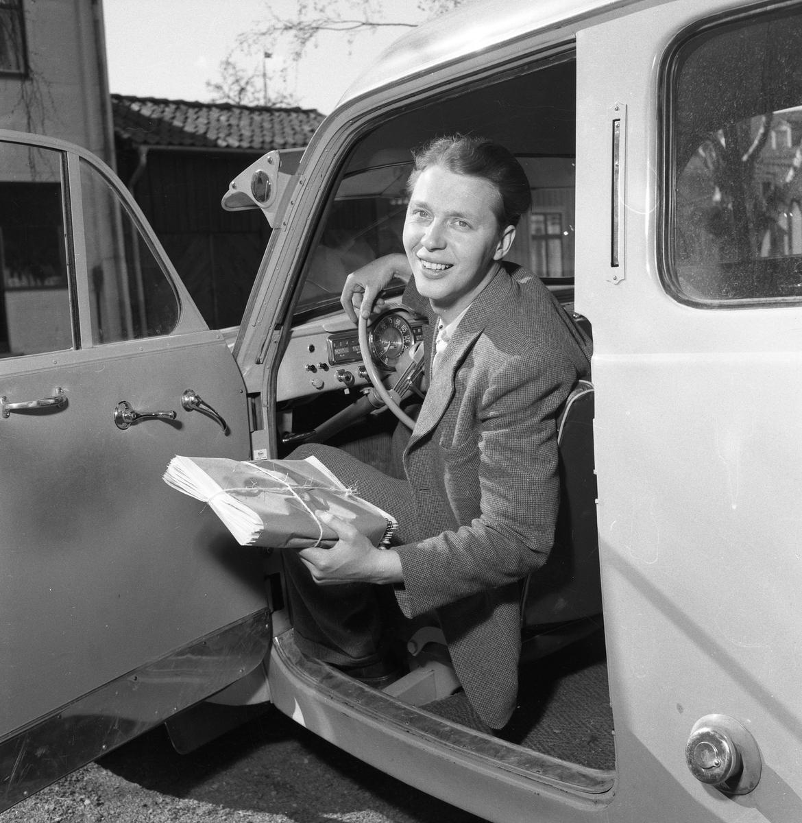 Arboga Tidning, personal. Willy Johansson sitter bakom ratten. Han har en bunt tidningar i handen. Interiör av bil, instrumentbrädan syns delvis.