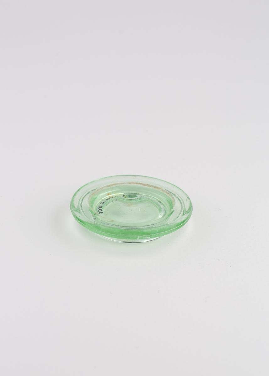 Rundt glasslokk som ligger løst oppå åttekantet glasskrukke.