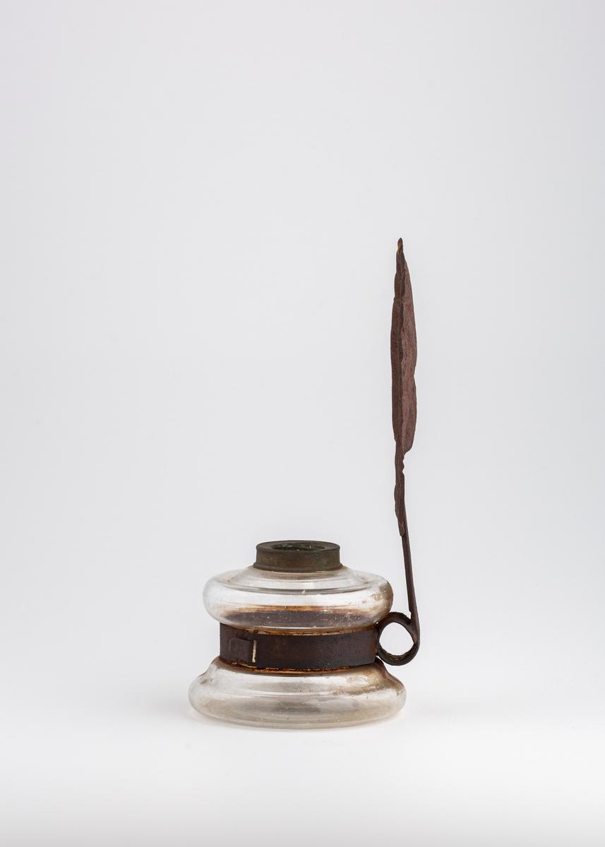 Lampen består av en glassbeholder som svinger inn på midten, og en bakplate i metall formet som et skjell. Bakplaten er festet til beholderen med en ring, og har en hals i metall. I halsen er det et hull for oppheng på vegg. Oppå beholderen er det en åpning hvor det sitter en metallring rundt. Parafinlampen mangler brenner og glasskolbe.