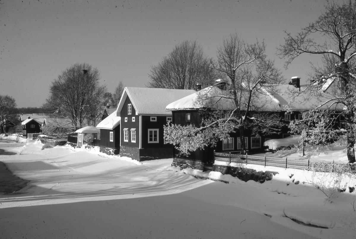 Utsikt från Kapellbron. Ågårdar i vinterskrud. Is och snö på Arbogaån. Fastigheterna ligger längs Västerlånggatan.