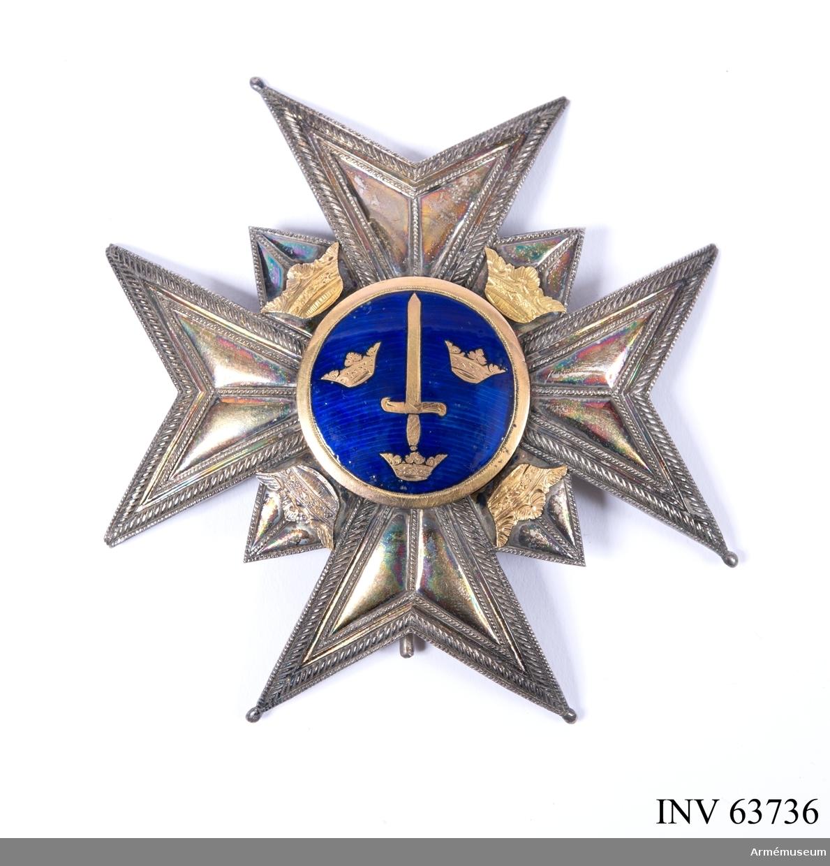 Grupp M II. Kraschan, kommendör av stora korset av Svärdsorden, tidigare tillhörande generallöjtnanten och friherren Bror Cederströms samling. Ett johannitkors av slätt silver med kluvna, strierade armar, mellan armarna uddar, var och en belagd med en krona av guld. Mittgloben av blå emalj inom en slät guldram, innehåller ett upprätt stående svärd omgivet av Sveriges tre kronor.