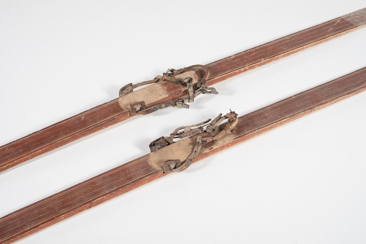 Skiene er bredest foran, og har jevn bredde ellers. Bindingene består av to lærremmer, med jernspenne til stramming. Skiene er tykkere på midten enn ellers. De er rette bak og spisse foran, hvor tuppen krummer oppover og har en tapp ytterst. Under skiene går det en renne i midten. Striper langs kantene og i midten oppå.