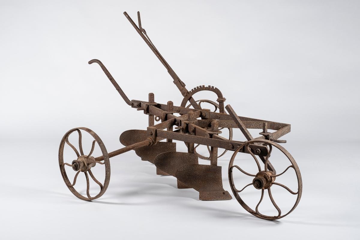 Plogen har fire små plogskjær som er montert på en ramme med hjul. Hjulene har lik dimensjon, og det er ett hjul foran og to hjul bak. Det ser ut til at minst to av hjulene kan høydereguleres. Plogen har et håndtak i bakkant, samt en spak for høyderegulering.