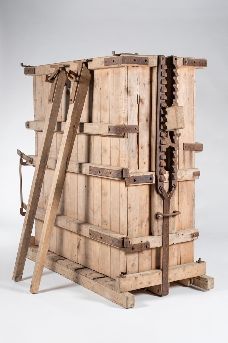 Høypresse som består av fire deler; kasse, lokk og to presstenger. Høypressen er av tre, og har ilegg ovenfra. I den ene langsiden er det en hengslet før for uttak av høyballen. Det er smidd jernbeslag i alle kassens hjørner. I kassen er det fire åpninger i bunnen og i bakre vegg for plassering av pressetrådene. På hver kortside av kassen er det en åpning for tverrstokken til lokket. På hver side av åpningene er det en tannrekke for presstengene og festing av lokket. Under tannrekkene er det et håndtak. I begge hjørnene på fremsiden er det kroker.