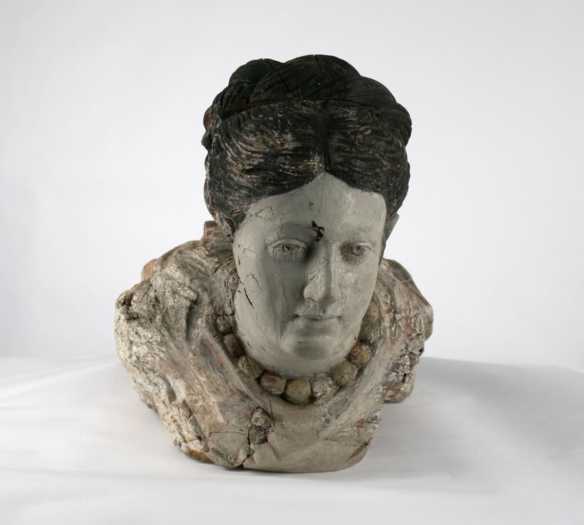Gallionsfigur av kvinnehode, med mørkt hår og halssmykke. Kun hode og øvre del av brystparti.