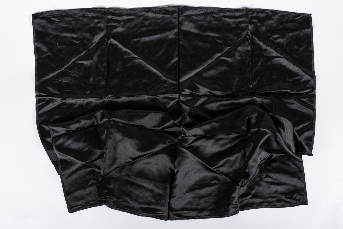 Firkantet tøystykke i sort sateng.