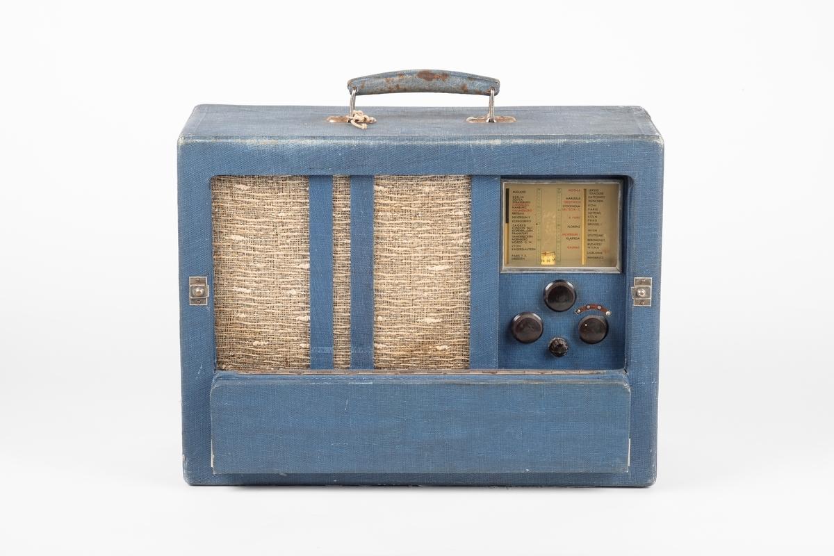 En radio kledd med blått tekstil. Radioen har lokk i front og kan bæres med håndtak. Lokket kan brettes sammen i to. Bak lokket er høyttaleren, kanaloversikt og 4 svarte vridere. På baksiden er det 4 hull og tilkobling av ledninger.