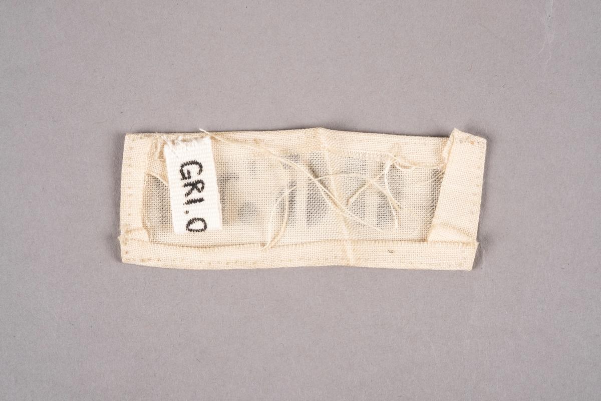 En merkelapp i hvit tekstil med trykket fangenummer i svart.