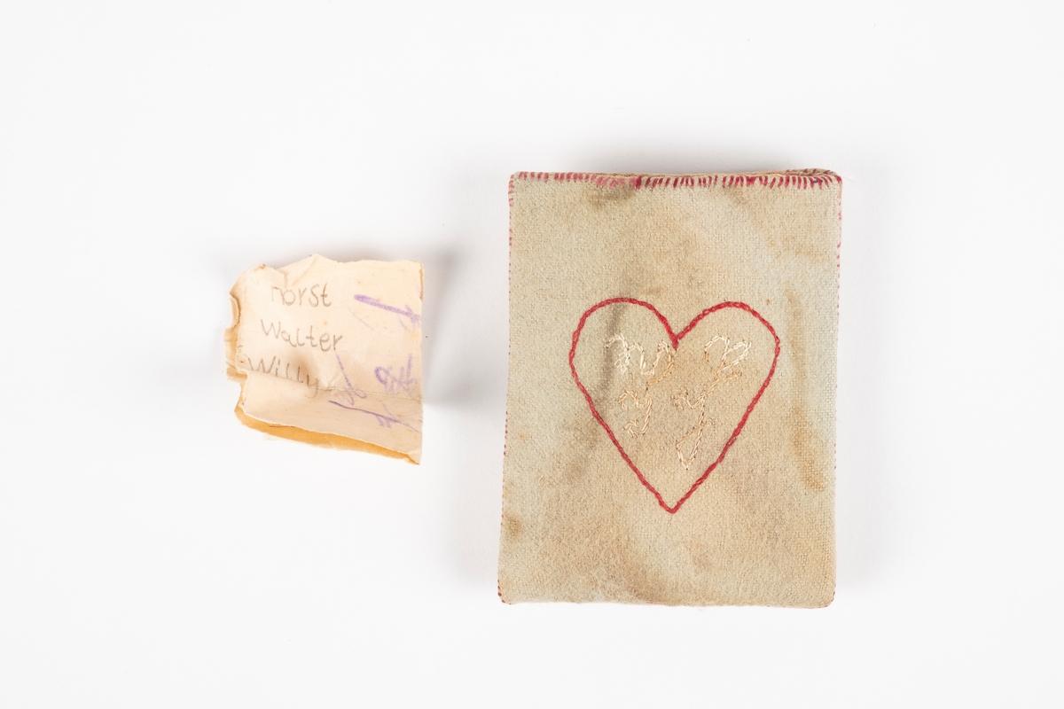En liten firkantet lomme laget av papp kledd med tekstil. Inne i lommen er det en papirlapp. Det er brodert ruter med årstall under på den ene siden og et hjerte med bokstaver i på den andre.