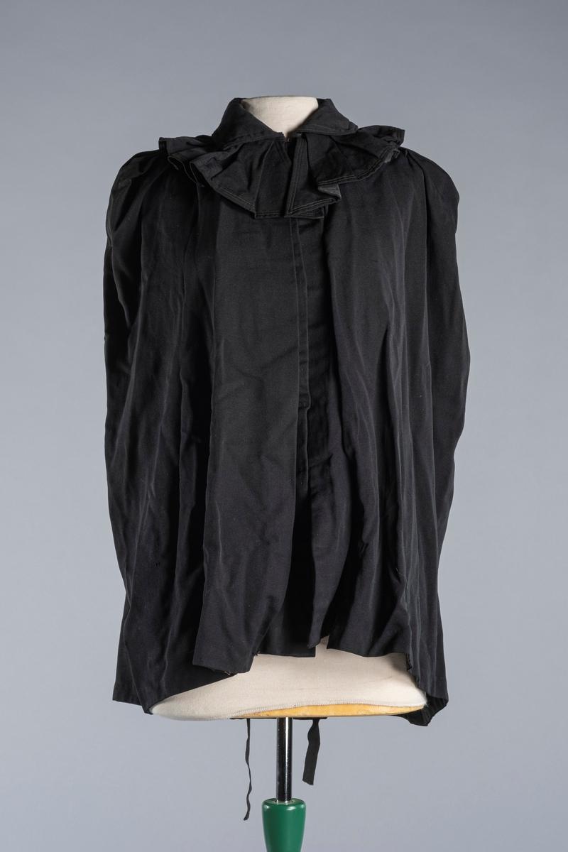 Cape i ull- og bomullsblanding . Kantbånd av silke i halslinningen og i kantene. Åpning framme, med 7 metallhemper for lukking av capen. Åpninger til armene.