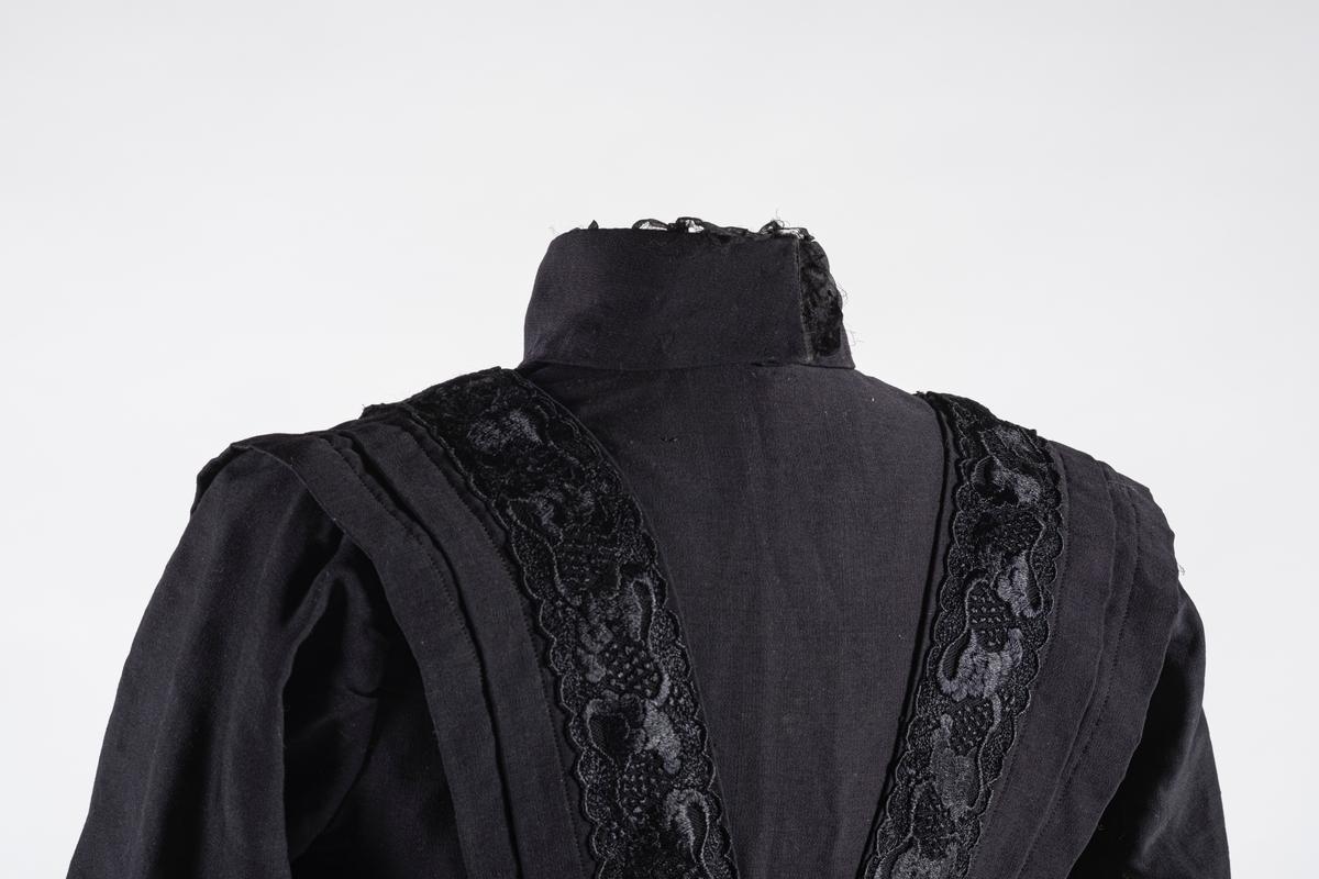 Kjole i 3 deler bestående av kjoleliv, skjørt og belte.  Kjolen er i svaft bomull og er hånd- og maskinsydd.  Kjolelivet har doble ermer. Nedre del på innerermen har opphøyde vertikale sømmer. Det samme har den midtre delen (klaffen) av forstykket. På hver side av klaffen er det påsydd blonder som strekker seg over skulderen og nedover ryggen i en V form. Langs disse blondene er det folder. Innsiden er fôret med lilla tekstil. Det er påsydd to svettelapper ved underarm-partiet og hempe ved hvert ermehull på innsiden. Kjolelivet har også fire spiler på innsiden. Kjolelivet lukkes med metallhekter og trykknapper. Fôret har egen lukning før ytterstoffet lukkes over. Halsen er høy og kneppes på baksiden med trykknapper. Det er to hekter på baksiden som skjørtet skal hektes i.  Skjørtet består av et forstykke i tre deler og bakstykke i 4 deler. Skjørtet er fôret med tynn bomull i svart med lilla skjær. Midjen har linning i lilla bomull. Skjørtet har forsterkningskant nederst med slitelist av bånd og floss. Det er påsydd to hemper i linningen. Skjørtet lukkes på baksiden med tre trykknapper. I linnengen er det påsydd en hvit tekstillapp med påskrift.  Beltet har fôring i lilla bomull. Det er folder langs beltet med rysjer i midten og ved hektepartiet. Beltet hektes sammen med metallhektere. Det er sydd inn 7 spiler i beltet.