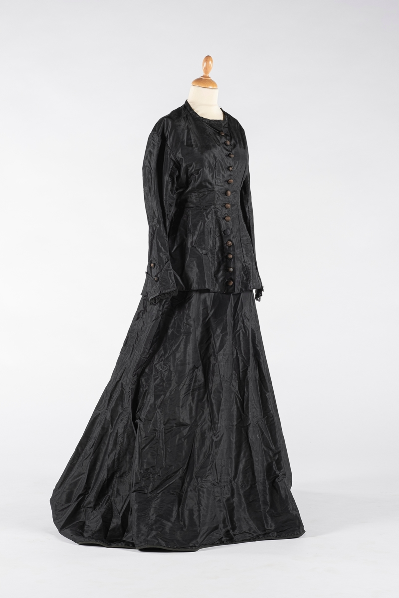 Todelt brudekjole bestående av kjoleliv og skjørt. Sort kjoleliv, figursydd med lange ermer og lav krage. Hovedtøy av taft, innvendig foret med linlerret og bomullstøy i ermene. Det er ingen spiler. Dekor av sorte kniplinger påsydd rundt ermene og to tøy-overtrukne knapper. Tøy-overtrukne knapper og maskinsydde knapphull på fremsiden. Hempe av mørkegrønt stoff i rygg. Sort skjørt av taft med håndsydd lomme av bomullstoff i siden. To små metallhekter og metallhemper i livet, med rynker i livet under hempene. bomullstoff i livet og i nedre kant av skjørtet. Hempe av mørkegrønt stoff i livet.