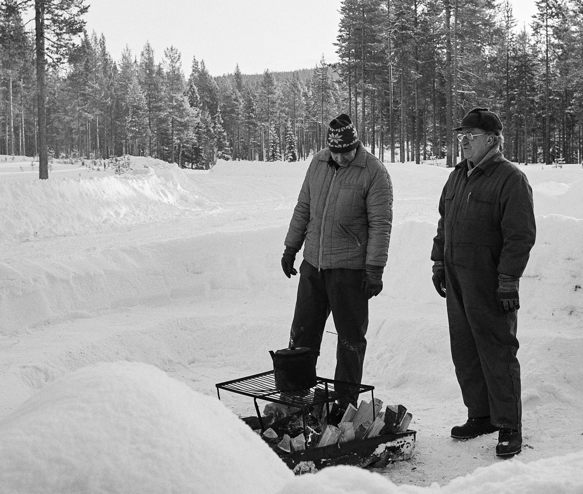 """Sveg 1984. Motortekniker Roland Svensson och tekniklärare Bengt Lundblad väntar på en kurs """"någonstans i skogen"""" för att genomföra ett vårdpass. Elden var den naturliga samlingspunkten för alla."""