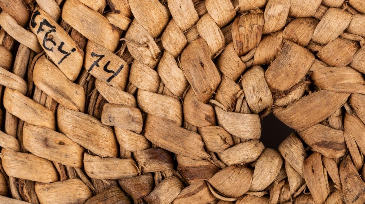 Rund, flätad av björkrötter. I sidorna urtaget som ett öppet gallerverk. Grep borta.