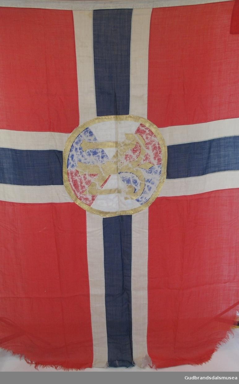 Norsk flagg med Den norske turistforenings logo påmalt i midten. Innsydd line øverst med metallhengsel i ene enden. I bruk på¨Sandhaug turisthytte frem til 1948.