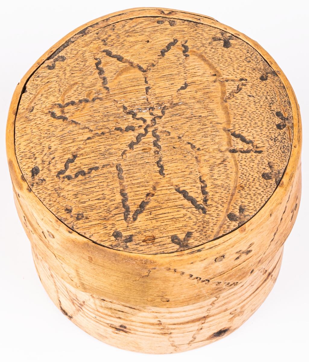 Ask, ornerad genom brännstämpling. I botten märkt 1783. I svepteknik, rund med lock. Botten och lock av ek. Ornament: fyrbladiga rosor samt krusiga linjer.