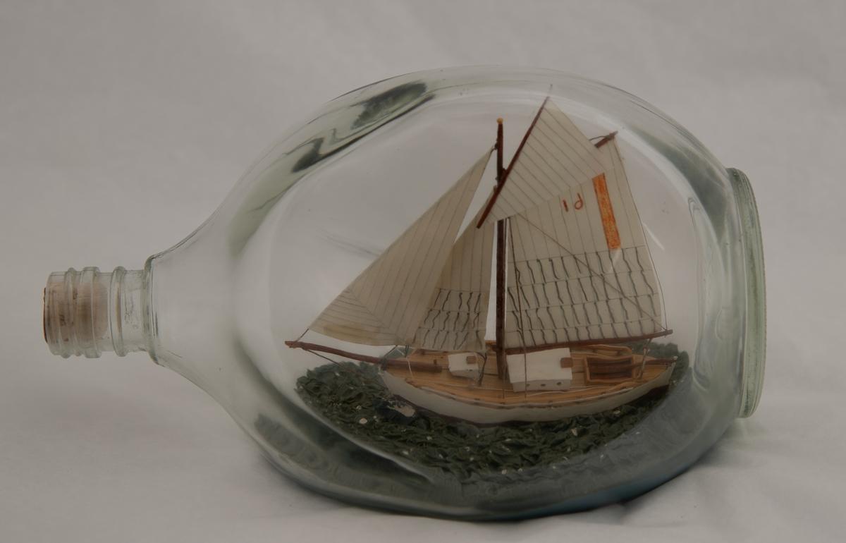 "Flaskeskute: ""Krabben"" , losbåt nr. l (Colin Archer)  Flaske i klart glass med trekantet form.  Hvitmalt skrog , brun under vannlinjen. Seil med oransje stripe og tallet 61 i oransje. Blågrønn sjø."
