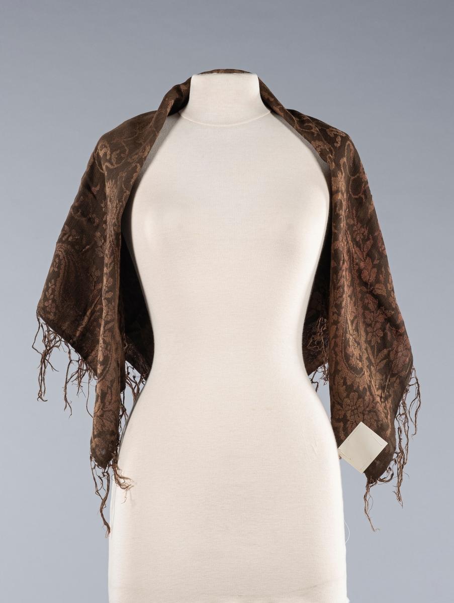 Rektangulært kobberfarget innslag sjal i bomull. På begge kortsidene er det en flettet kant med knyttede frynser ytterst. Sjalets underside er lysere enn oversiden.
