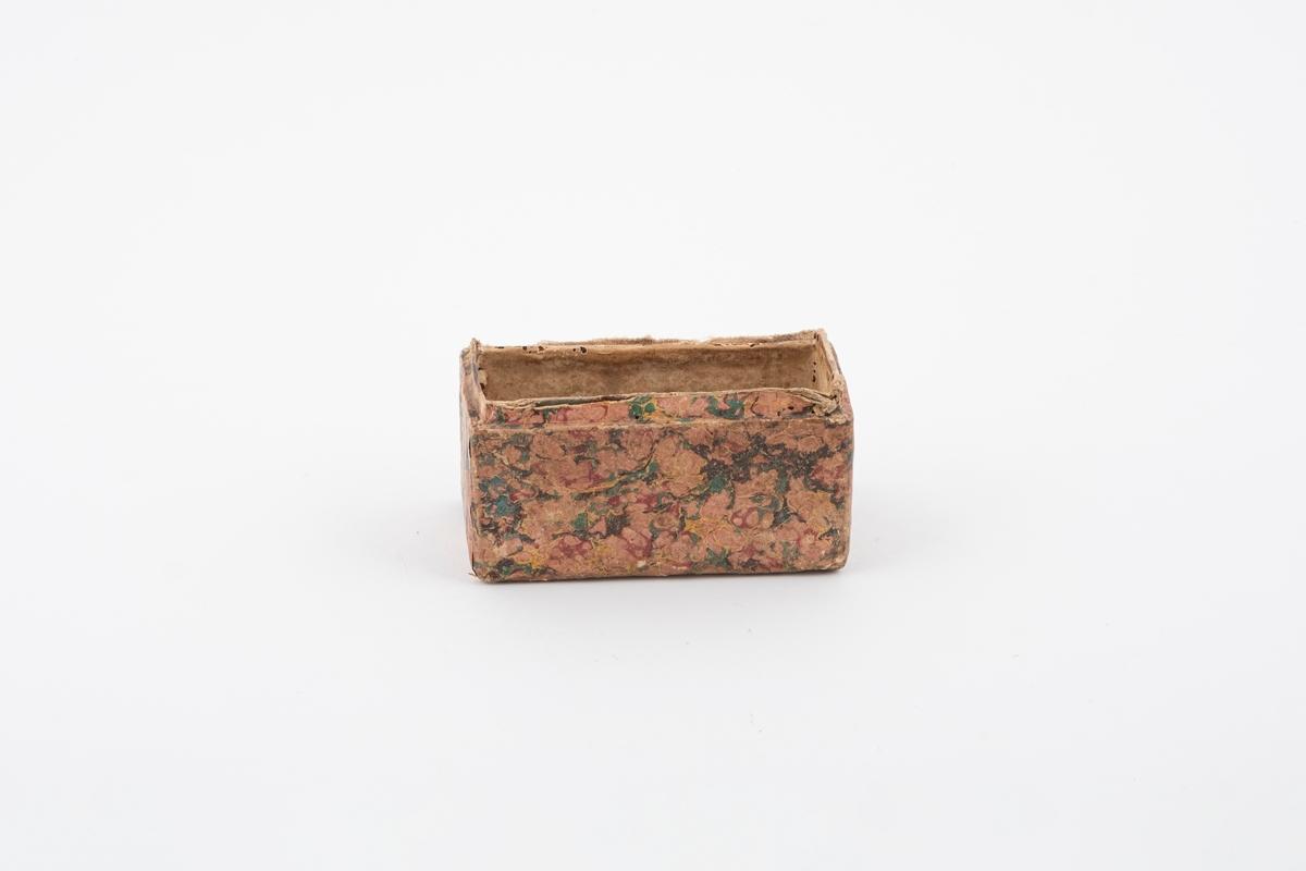 Bunn til skrin av papp. Den er kledd med tynt papir med mønster, både på innsiden og utsiden. På bakre øvre kant er det pålimt et tekstilbånd som tidligere har holdt lokket og bunnen sammen.